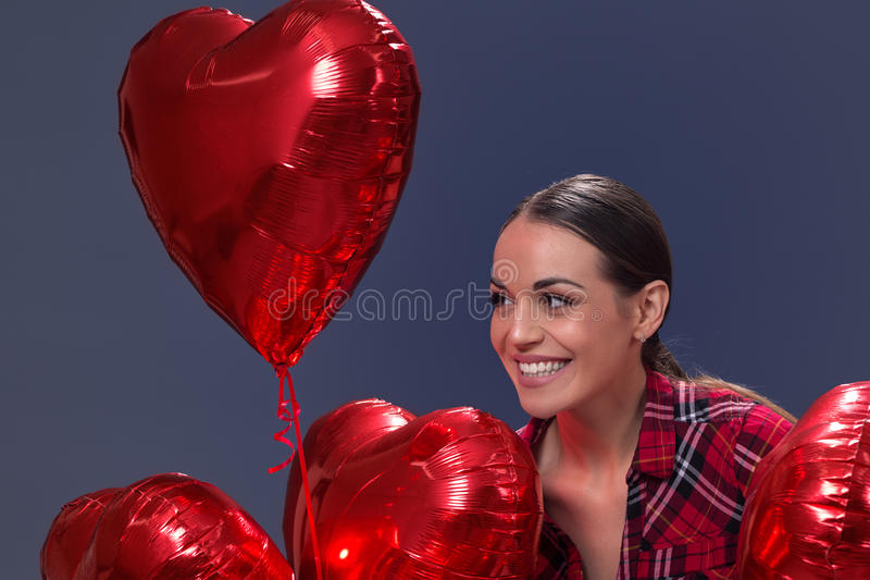Love - woman smiling with red heart shaped balloon royalty free stock photos