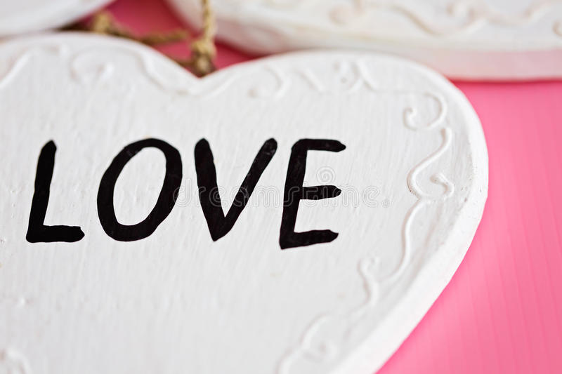 Love Wooden white heart on pink background, horizontal composition stock photos
