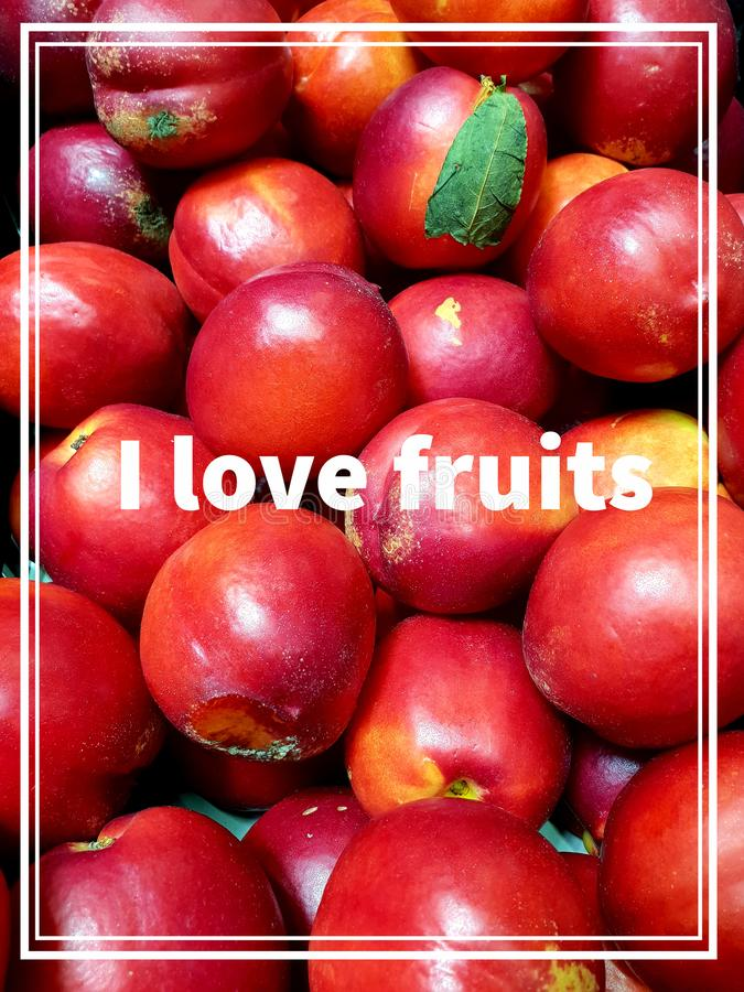 The word I love fruits text on a bunch of beautiful delicious red juicy plums. Healthy food lifestyle concept. Love word fruits text bunch beautiful red royalty free stock photo