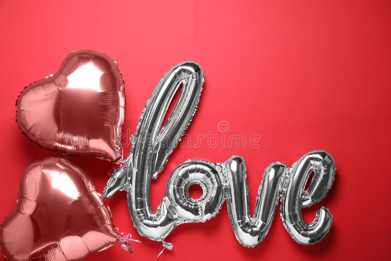 LOVE word and heart balloons on red background, flat lay. LOVE word and heart balloons on red background royalty free stock photography
