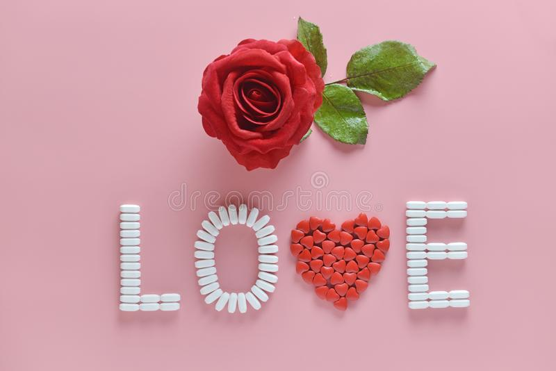 LOVE word made from medicine pills and red rose on pink background. Concept of Valentine`s Day. Or pharmacy, Medical stock photos
