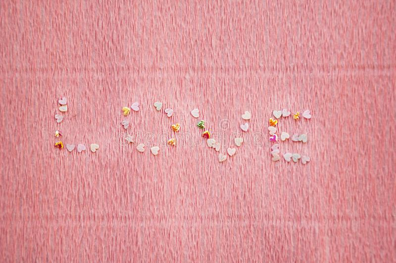 Love word made of sequins, shimmer and confetti on pink background. Love word made of heart shaped of sequins, shimmer and confetti on textured pink background stock photos
