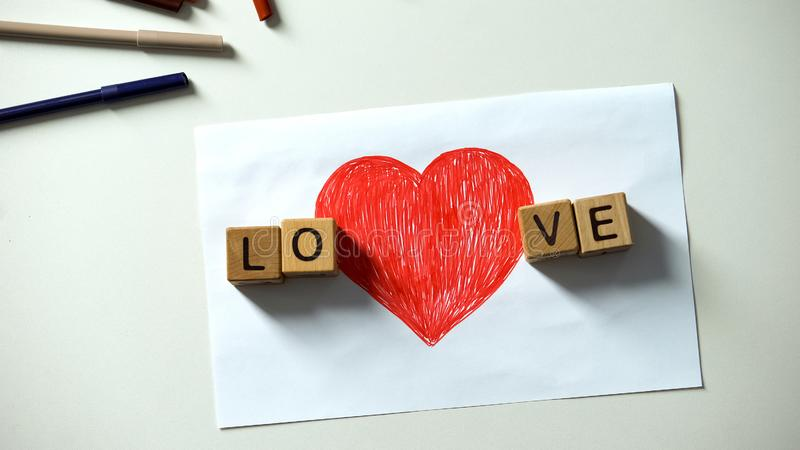 Love word made of wooden cubes lying on sides of red heart drawing, sincerity. Stock photo royalty free stock photos