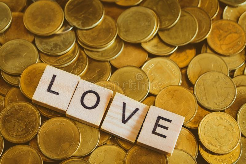 Love word on wooden blocks on gold coin money stock photo