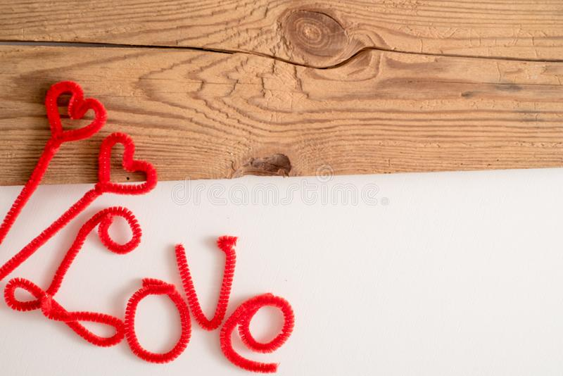 Love is a word is written spelling font. The word love red. White background, wooden table. Space for text. Love is a word is written spelling font. The word stock image
