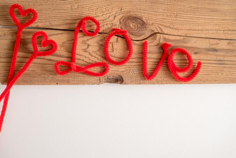 Love is a word is written spelling font. The word love red. White background, wooden table. Space for text. Love is a word is written spelling font. The word royalty free stock image