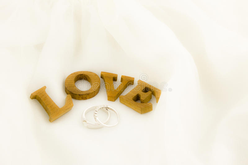 Love wording and rings on soft white dress stock photography