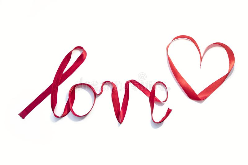 `love` written with red silk ribbon stock images
