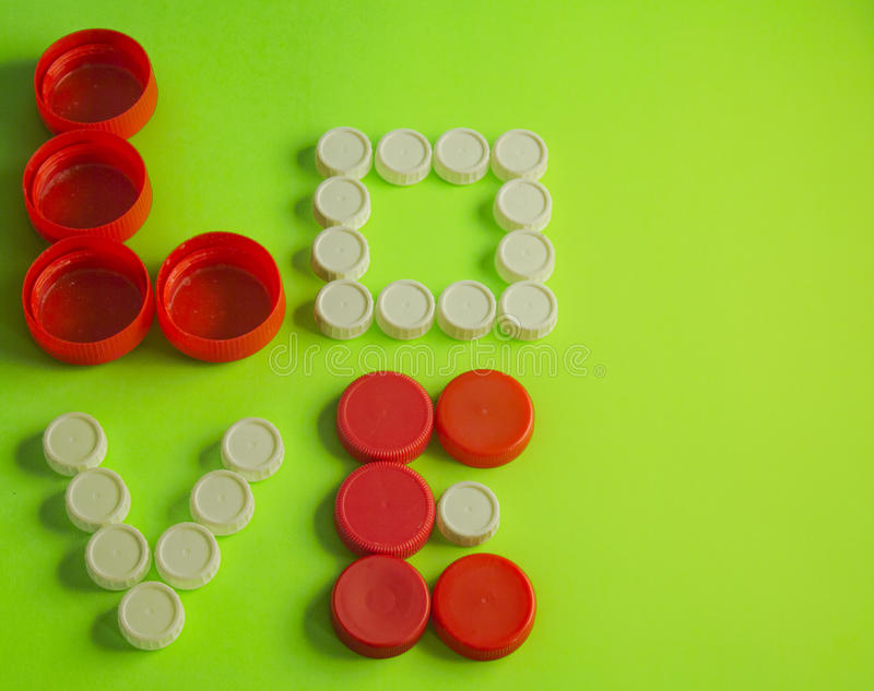 Love written with red and white bottle tops on a green background stock photos