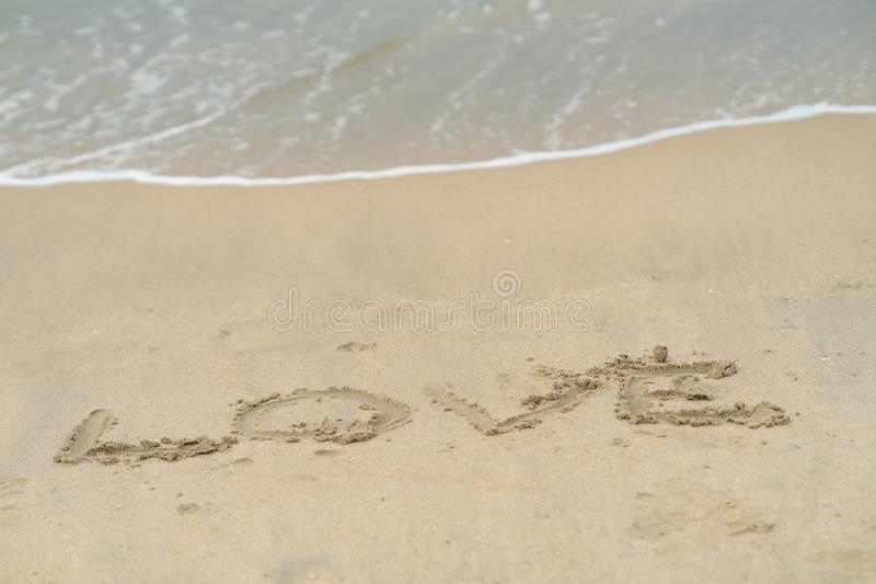 Love written on sand, in the background soft waves with foam of ocean on the sandy beach stock photography