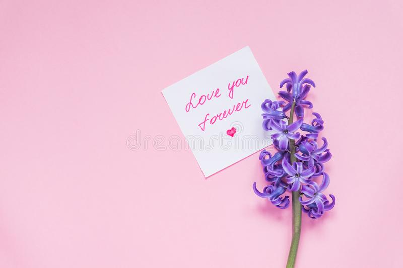 Love you forever paper tag and purple hyacinth flower on wooden table. Top view, miniml flat lay.  royalty free stock image