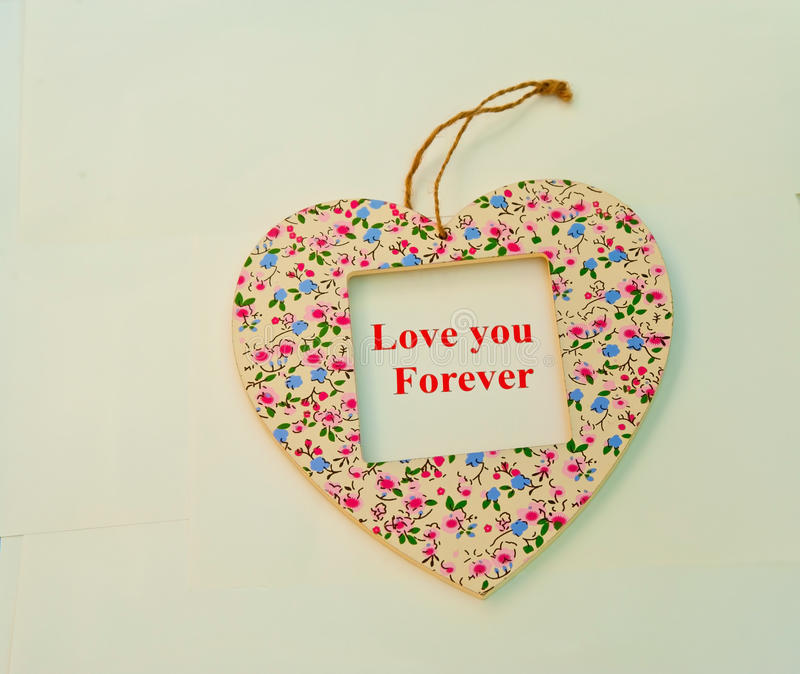 Love you forever. Text love you forever in red letters in the square aperture of a heart shape with floral decoration, cream background royalty free stock photography