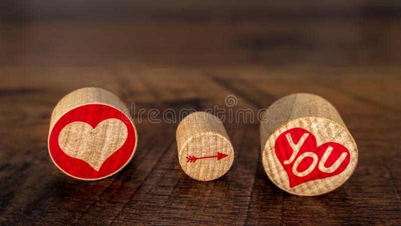 Love You with red hart pointing arrow on You in red hart on cork pieces Valentine's Day idea on vintage oak front view. Love You symbols on 3 oval pieces stock photo