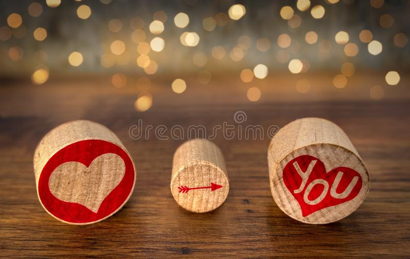 Love You sign, red hart, pointing arrow on You in red hart on oval cork pieces, Bokeh and vintage oak as background, front view. Love You illustrated with red stock photography
