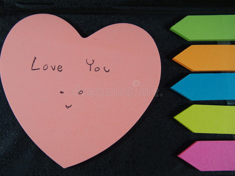 Love you with smiling face, drawing and writing on pose its paper with colorful heart and arrow on black leatherette background. Feeling happy, fall in love you royalty free stock photos