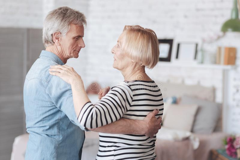 Charming elderly couple dancing at home royalty free stock images