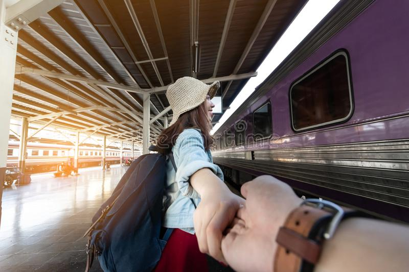 In love young Asian woman holding boyfriend hands follow her at train station. Romantic and travel in summer vacation concept stock images