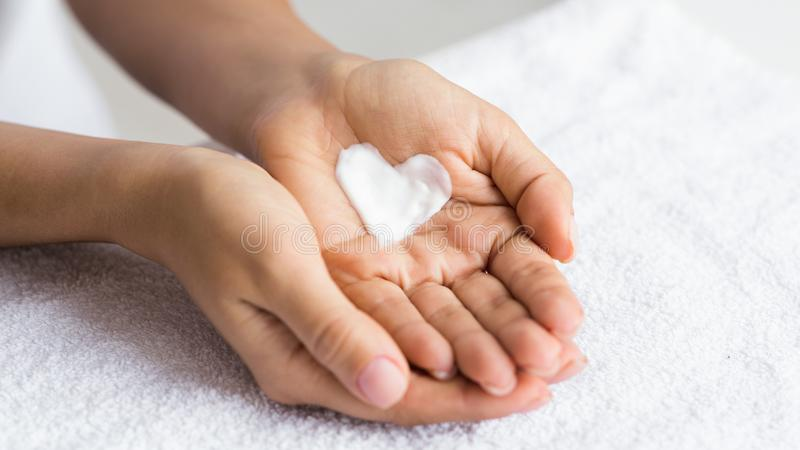 Love your body. Female hands with cream in heart shape royalty free stock photography