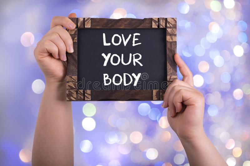Love your body. A woman holding chalkboard with words love your body on bokeh light background stock image