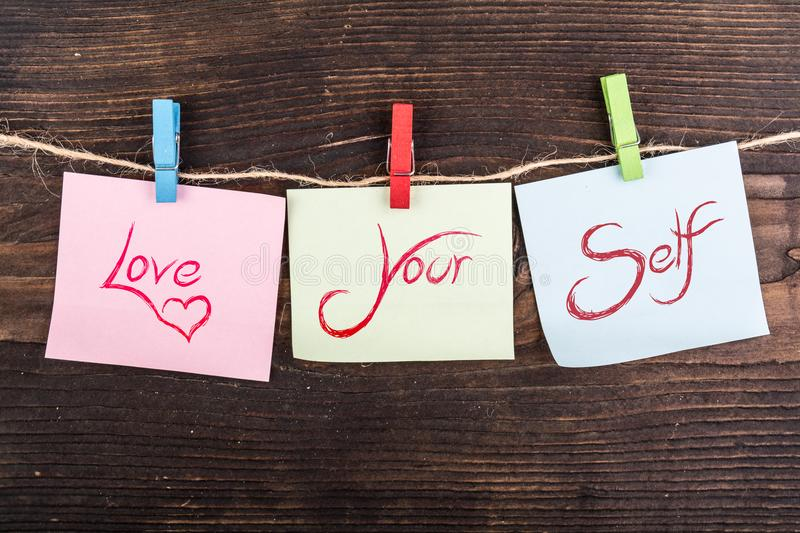 Love your self note. Love your self in sticky notes hanging by clothespin on wood royalty free stock photos