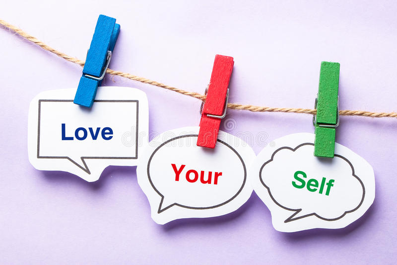 Love your self. Paper bubbles with clip hanging on the line against purple background stock images