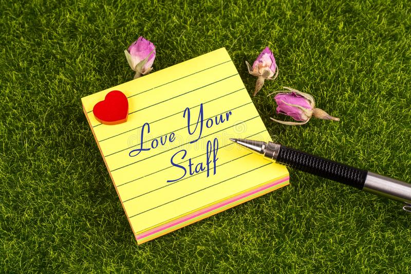 Love your staff note. Love your staff in sticky note with heart , pen and dried rose on grass stock photo