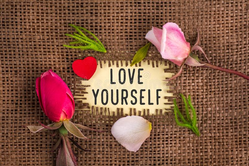 Love yourself written in hole on the burlap. With rose flowers and wooden red heart royalty free stock photos