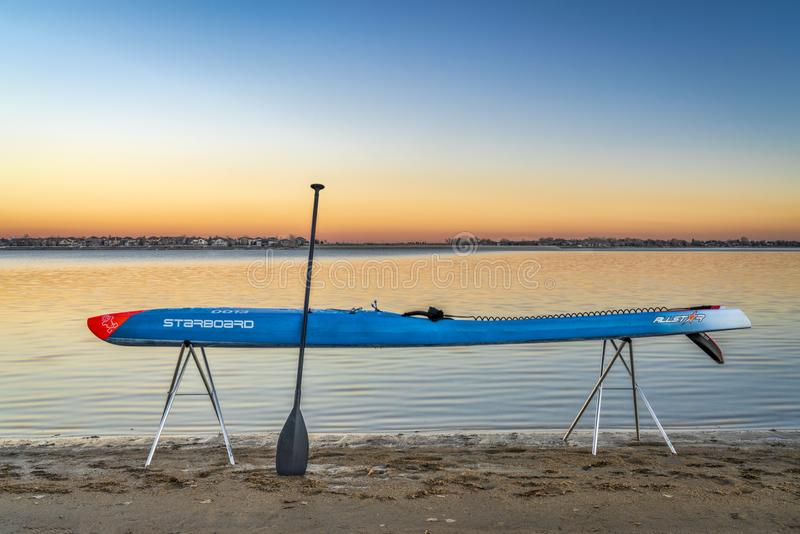 Racing stand up paddleboard on stands. Loveland, CO, USA - November 20, 1918: Dusk over a lake after paddling - a racing stand up paddleboard by Starboard on royalty free stock images