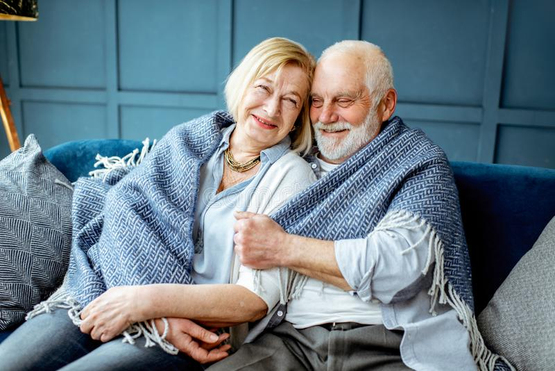 Lovele senior couple wrapped with plaid at home stock photography