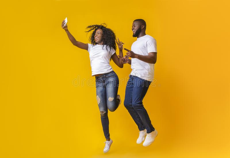 Lovely african guy and girl taking selfie while jumping. Smiling African Couple Is Taking Selfie While Jumping, pointing at camera, showing victory sign, yellow royalty free stock images