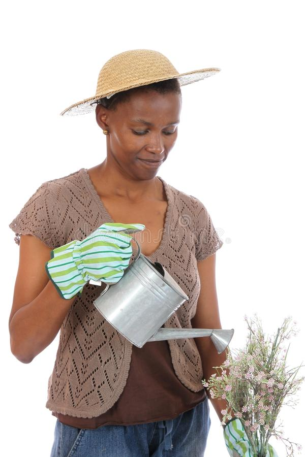 Lovely African Woman Gardener. Pretty African wowan with watering can and flowers stock image
