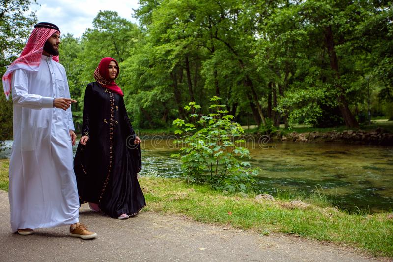Lovely arabian couple in traditional clothes embracing outdoors.  royalty free stock image
