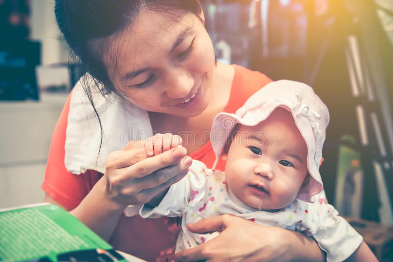 Asian mother smiling and take care her daughter with love. Vintage tone. stock image