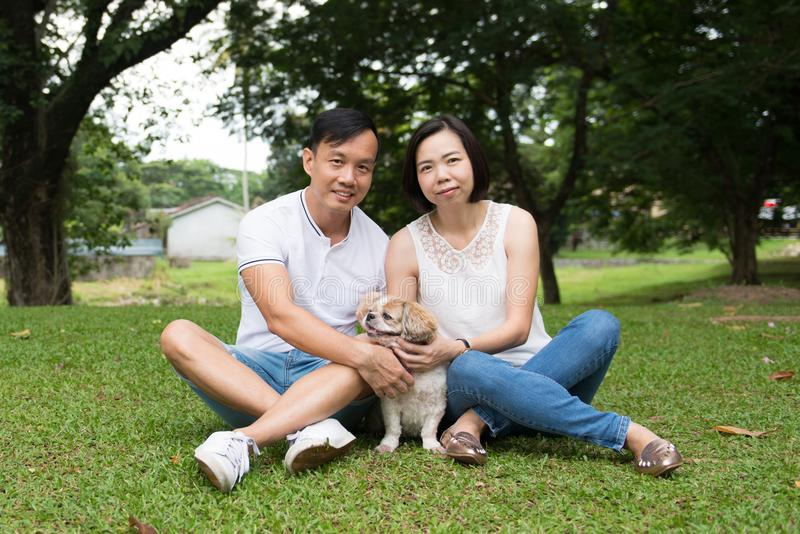 Asian lovely couple with shih tzu dog. Lovely asian couple with their pet shih tzu puppy at outdoor park royalty free stock image