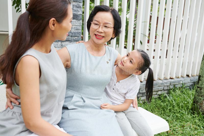 Lovely Asian family sitting outdoors royalty free stock photo
