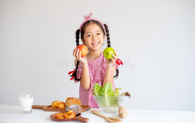 Lovely Asian little girl hold apples and smile with vegetables, milk and bread on table with white wall background royalty free stock photos