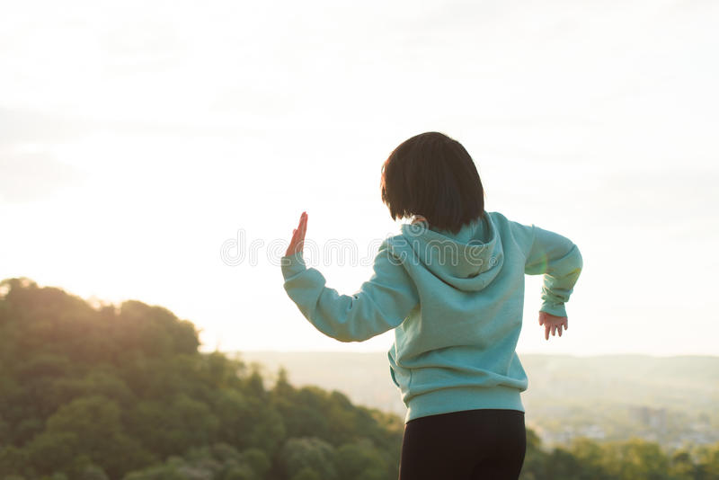 Lovely asian woman stretching on the blue sky background. Moment of relaxing and recreating royalty free stock photography