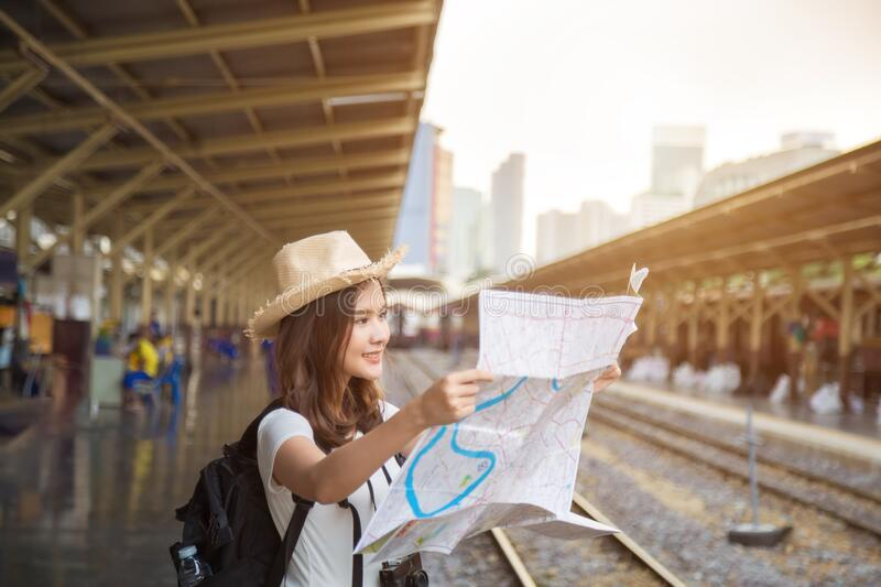 Lovely Asian woman traveler smiling and watching a map for journey`s planning in vacation royalty free stock images