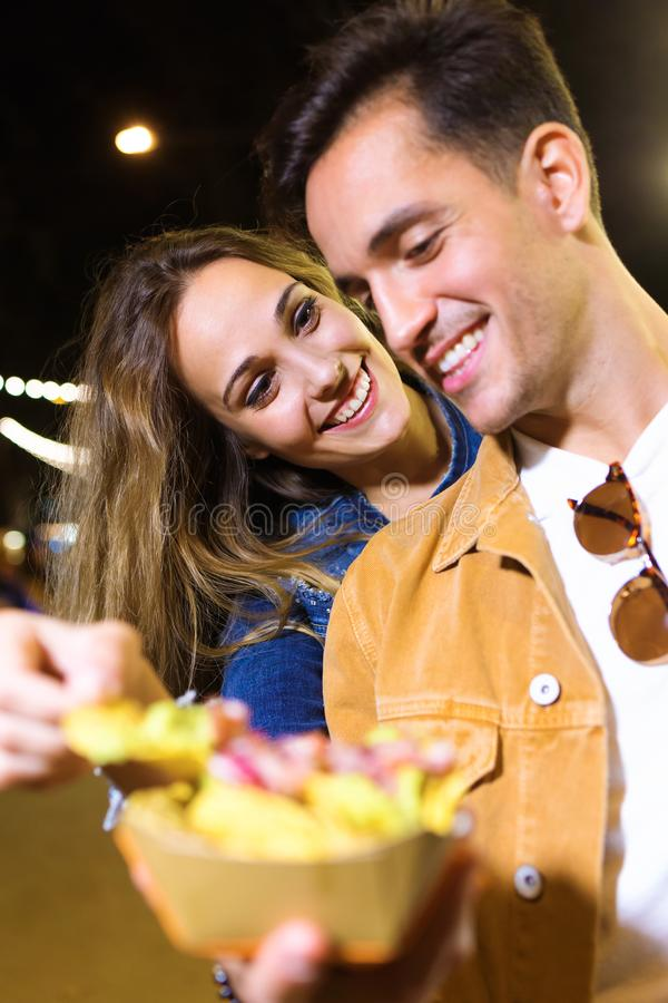Lovely attractive couple eating potatoes together in eat market in the street. Shot of lovely attractive couple eating potatoes together in eat market in the royalty free stock photo