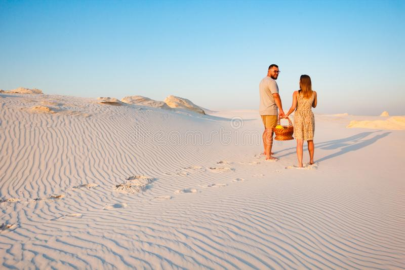 Lovely attractive couple on the white sand beach or in the desert or in the sand dunes, guy and a girl with a basket in their stock photos