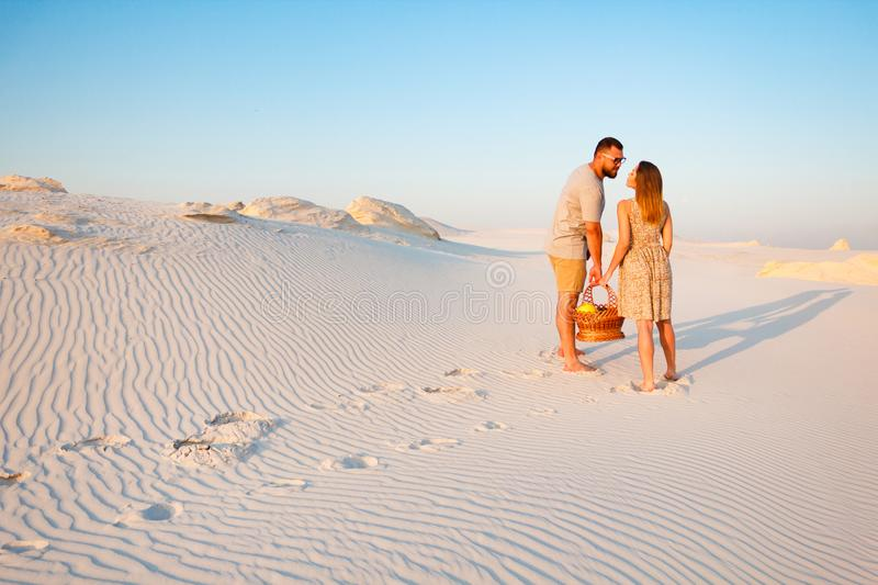 Lovely attractive couple on the white sand beach or in the desert or in the sand dunes, guy and a girl with a basket in their stock photo