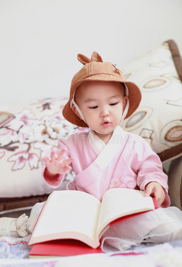 Lovely Baby girl With a hat reading book sit down on sofa stock photos