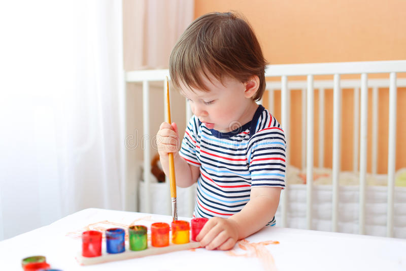 Lovely baby painting at home stock photos