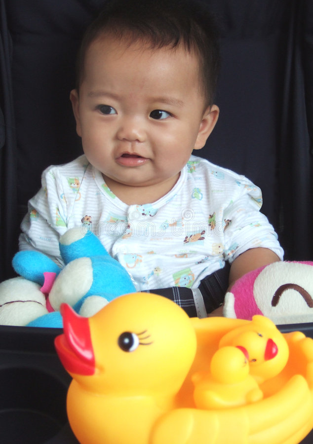 Lovely baby and toys. With black background stock photography