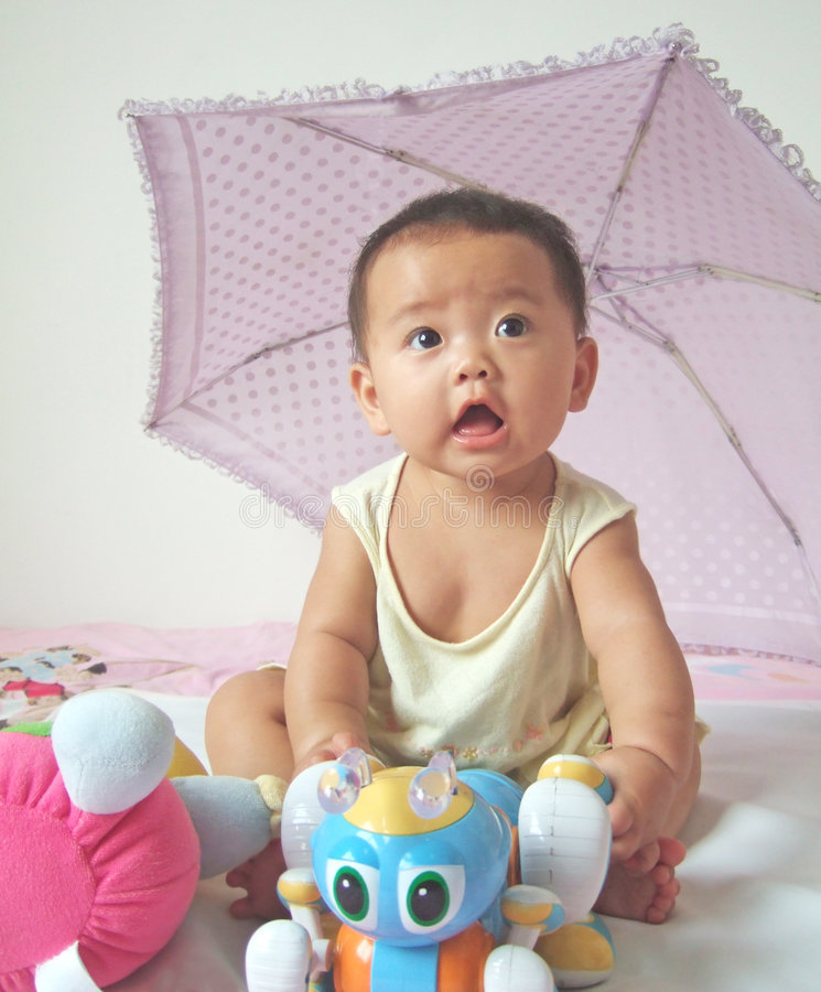 Lovely baby and toys. On a bed stock images