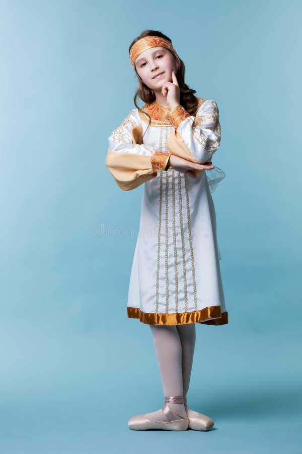 Lovely ballerina in folk costume posing at camera stock image