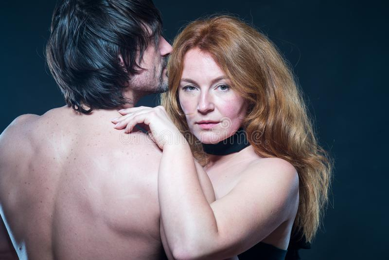 Lovely bare shouldered woman gently embracing her husbands shoulder royalty free stock photography