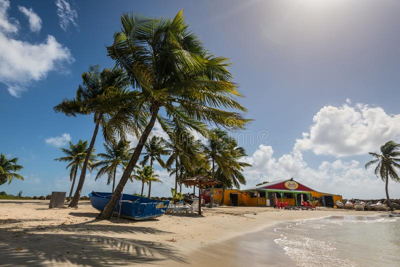 Lovely beach in Gosier, Guadeloupe. Le Gosier, Guadeloupe - December 20, 2016: Paradise Lovely beach, palm trees and shop near Le Gosier in Guadeloupe, an stock photography