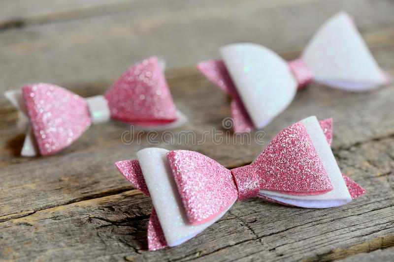 Lovely beautiful bows for hair. Pink and white shiny felt bows for girls. Beautiful hair accessories set on a wooden table royalty free stock photo