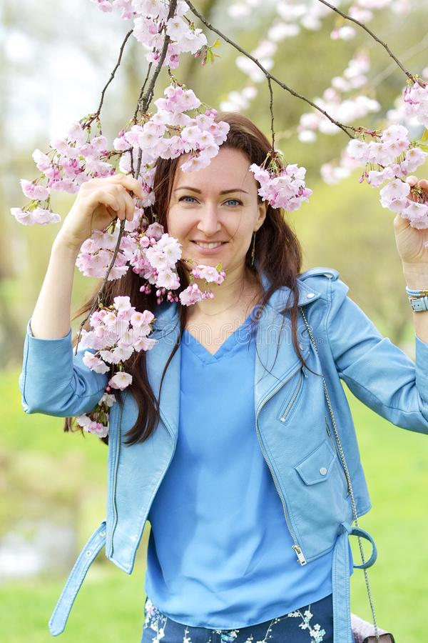 Lovely Beautiful Caucasian Woman Standing Posing on the Background of Blooming Japan Cherry royalty free stock photos